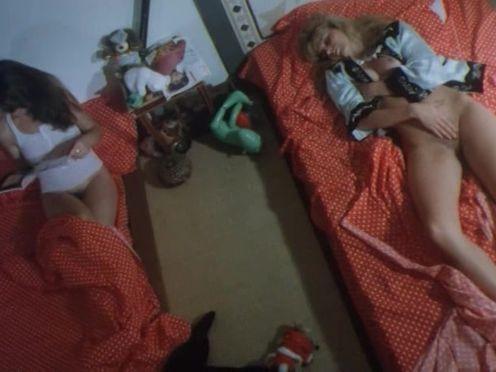 Блонда ласкает себя, лежа в красной постели при подружке