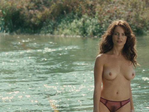 Красивая женщина купается без купальника в реке